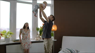 stock-footage-young-father-throws-baby-into-the-air-young-family-at-the-window